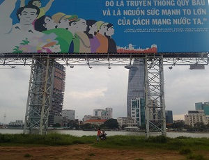 Temporary propaganda billboards dot the pre-development landscape as two young boys enjoy the riverview before the largest skyscraper in Ho Chi Minh City.