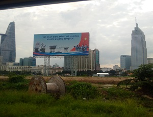A wooden roll empty of coil sits in grassland, rapidly to be replaced by some of the largest developmental projects and buildings Vietnam has ever seen in its history. The billboard above talks about defending Vietnam's sea borders.